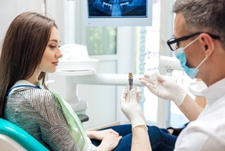 A dentist discussing dental implants with a patient