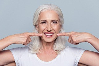 Older woman pointing to her smile