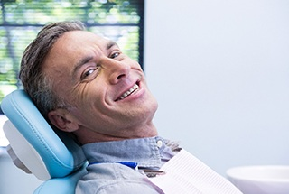 Man sitting back in chair smiling after seeing emergency dentist in McKinney, TX