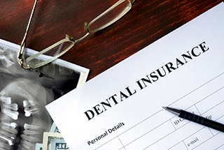Dental insurance form on desk with X-ray