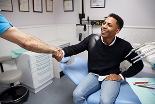 Man sitting on chair shaking hands with dentist