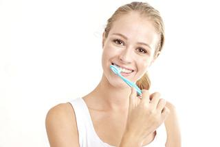 woman in white shirt brushing teeth against light background