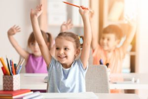 child in class raising their hands