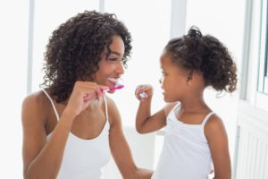 Smiling mother teaching her young daughter how to brush her teeth