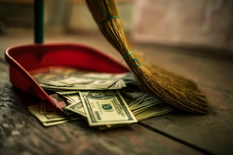 Money being swept into dustpan
