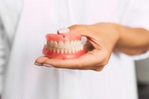 dentist holding a set of full dentures in McKinney